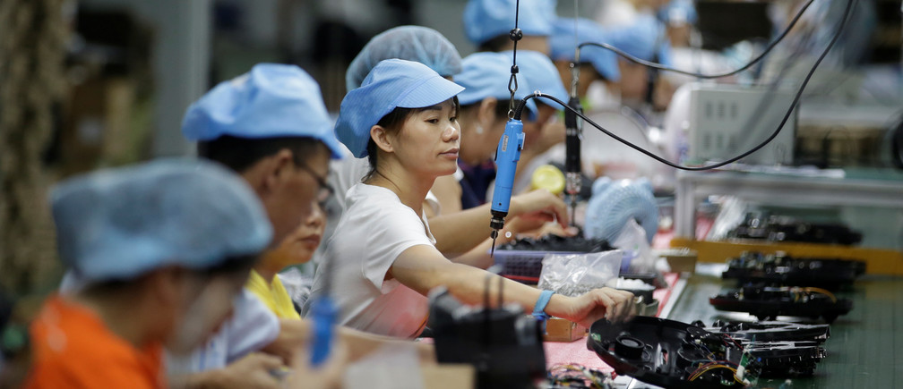 Employees work on the production line of a robot vacuum cleaner  factory of Matsutek in Shenzhen, China August 9, 2019. Picture taken August 9, 2019. REUTERS/Jason Lee - RC1AA8FAFB80