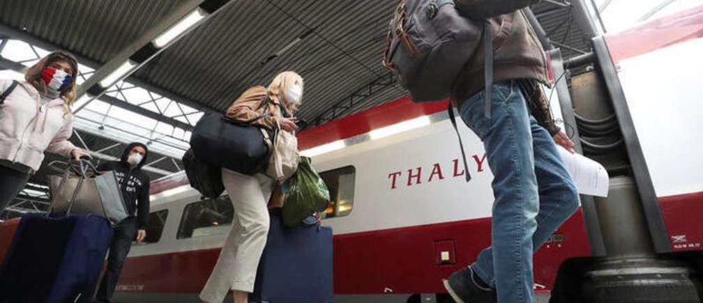 Passengers wearing protective face masks walk to board a Thalys high-speed train to Paris at Zuid-Midi station on the first day of the easing of lockdown measures, during the outbreak of the coronavirus disease (COVID-19), in Brussels, Belgium, May 4, 2020. REUTERS/Yves Herman