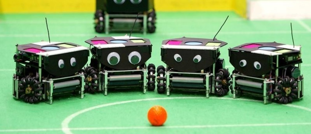 A team of robots stand before the ball prior to the start of theirmatch during the seventh Soccer World Championship for Robots in Padua,northern Italy, July 9, 2003. Robocup is an international research andeducation initiative aimed at fostering artificial intelligence androbotics research. REUTERS/Max RossiMR/JV - RP4DRHYKRSAA