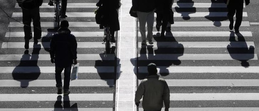 People walk on a crosswalk in Tokyo January 11, 2011. Japan's index of coincident economic indicators rose a preliminary 1.4 points in November from the previous month, the Cabinet Office said on Tuesday, up for the first time in three months. REUTERS/Yuriko Nakao (JAPAN - Tags: EMPLOYMENT BUSINESS)