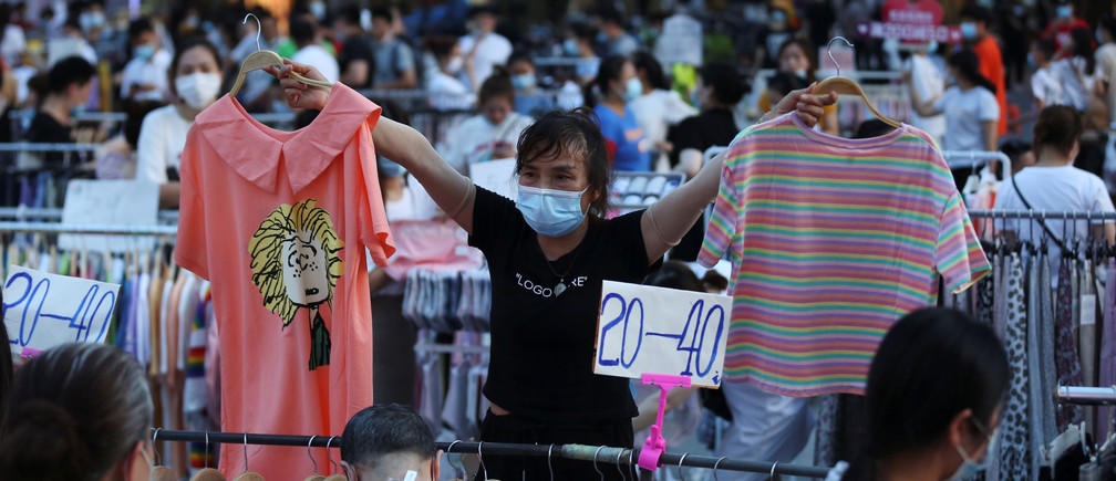 Un vendedor con una máscara facial después del brote de la enfermedad coronavirus (COVID-19) sostiene artículos de ropa para vender en un puesto callejero en la carretera Jianghan en Wuhan, provincia de Hubei, China, el 8 de junio de 2020.