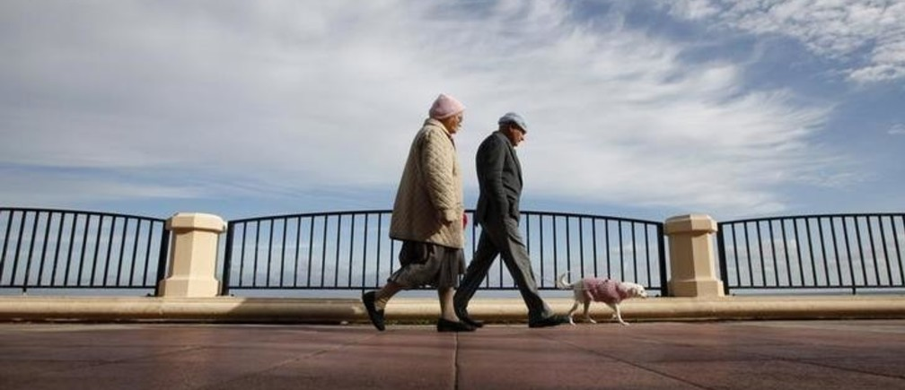 An elderly couple walk their dog along the promenade in Sliema, outside Valletta December 30, 2010. REUTERS/Darrin Zammit Lupi (MALTA - Tags: SOCIETY ANIMALS IMAGES OF THE DAY) MALTA OUT. NO COMMERCIAL OR EDITORIAL SALES IN MALTA