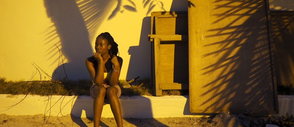 A woman sits under a palm tree at dusk after a block party in Abidjan, Ivory Coast, September 12, 2015.