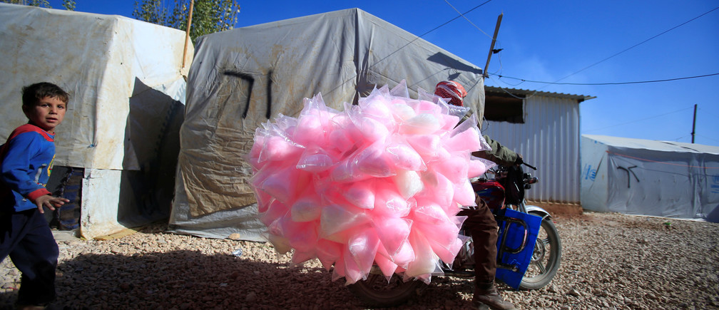 A Syrian refugee boy walks behind a cotton candy vendor at al-Rawda refugee camp in the Bekaa valley, Lebanon November 24, 2016. REUTERS/Ali Hashisho      TPX IMAGES OF THE DAY - RC19BF1F7C20