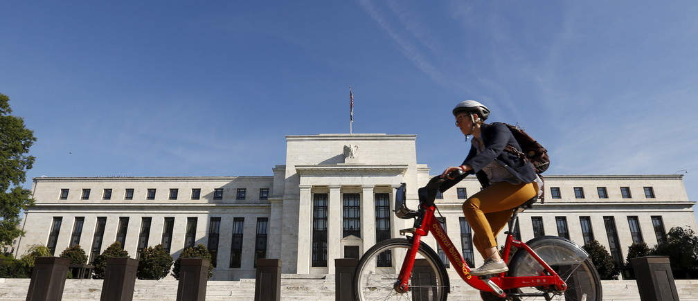 A cyclist passes the Federal Reserve headquarters in Washington September 16, 2015.