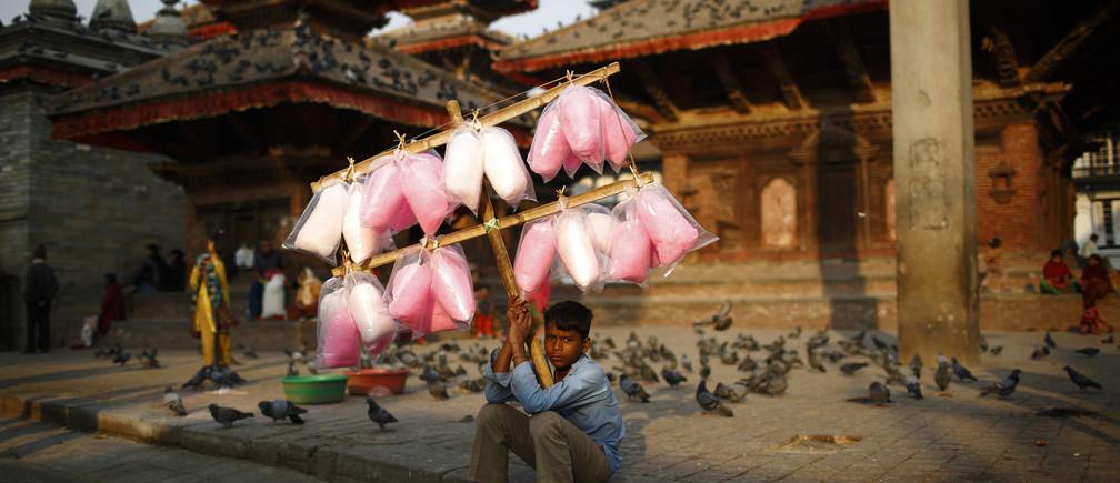 Satrohan Kumar Sahani, 12, sells cotton candy as he waits for customers along the street at Hanumandhoka Durbar Square in Kathmandu March 18, 2013.
