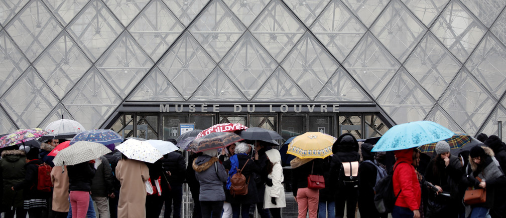 Les touristes font la queue pour entrer au Louvre alors que le personnel a fermé le musée lors d'une réunion du personnel sur l'épidémie de coronavirus, à Paris, France, le 2 mars 2020.