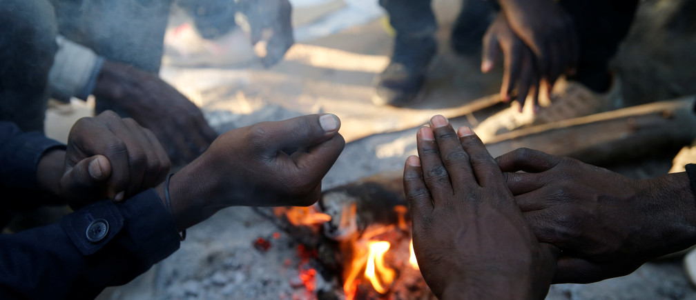 Sudanese migrants warm their hands over a wood fire in Ouistreham, France, October 30, 2017. REUTERS/Pascal Rossignol - RC131FAAA9B0