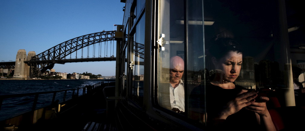 A commuter uses her mobile phone as a Circular Quay to Cockatoo Island ferry passes under the Sydney Harbour Bridge, November 24, 2015. Sydney's ferry system has been its lifeblood since the mid 1800s, transporting more than 15 million individual passenger journeys each year, according to the Bureau of Transport Statistics. From fast-food employees to finance industry executives, more than 40,000 trips are taken every day. Picture taken November 24, 2015. REUTERS/Jason Reed - RTX1WGVL