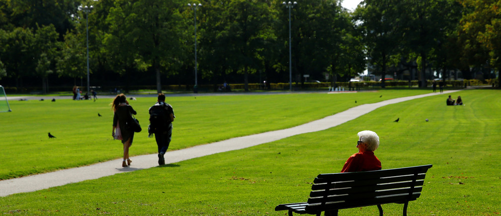 An elderly woman sits on a bench in a park, ahead of a national vote on pensions reform, in Lausanne, Switzerland September 22, 2017. REUTERS/Denis Balibouse - RC1712B4EF80