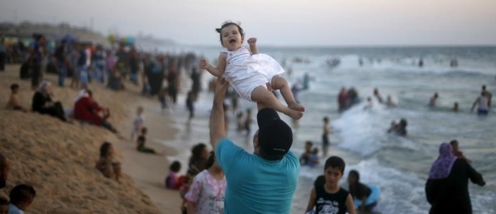 A Palestinian man lifts his daughter as he enjoys the warm weather with his family on a beach along the Mediterranean Sea in the northern Gaza Strip July 24, 2015. REUTERS/Mohammed Salem - GF10000169084