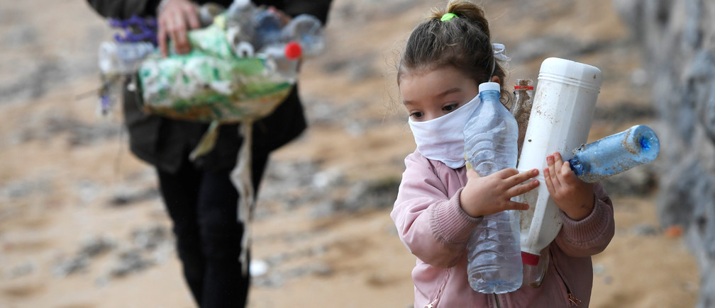 Alexandre and his daughter Alejandra go for a walk and collect plastic along the beach after the restrictions for children were partially lifted for the first time in six weeks, during the outbreak of coronavirus disease (COVID-19) in Gijon, Spain, April 26, 2020. REUTERS/Eloy Alonso - RC2CCG9CX8L5