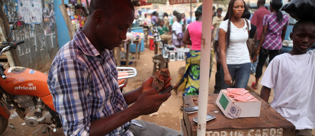 Alpha Abdulai Barrie, a 22-year-old agent for telecoms firm Africell, sits at his stall at Lumley Junction in Sierra Leone's capital Freetown December 13, 2012.