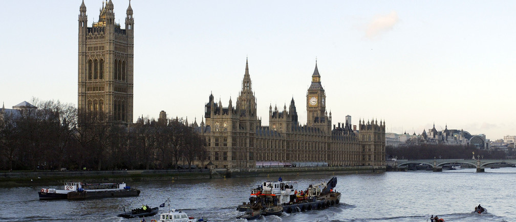 The barge carrying the northern bottle-nosed whale rescued from the river Thames passes in front of the House of Parliament in London January 21, 2006. Divers began on Saturday a critical operation to examine and, if possible, rescue a northern bottle-nosed whale that has strayed up the River Thames. REUTERS/Rob Dawson - RP3DSFDXOIAB