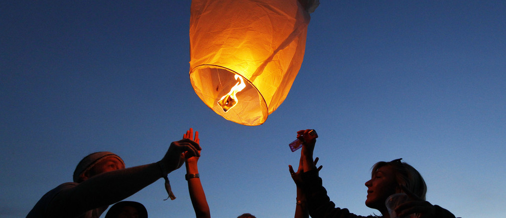 Festival goers set off paper lanterns at nightfall at the Glastonbury Festival 2010 in south west England, June 23, 2010. Glastonbury, one of the top summer music festivals in western Europe, runs from June 23-27. Picture taken June 23, 2010. REUTERS/Luke MacGregor (BRITAIN - Tags: ENTERTAINMENT SOCIETY) - GM1E66O1H4801
