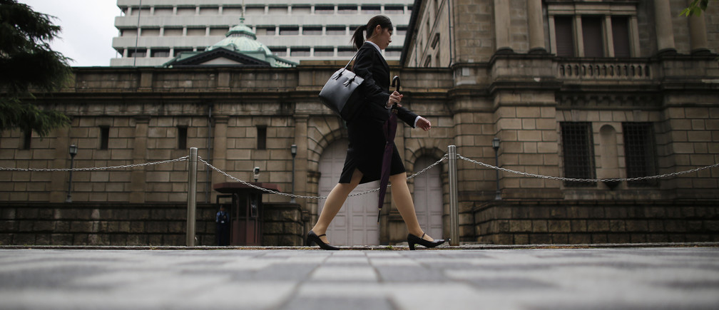 A woman walks past the Bank of Japan headquarters in Tokyo July 2, 2012. Japanese manufacturers were less pessimistic about business conditions in the three months to June, the central bank's closely watched tankan survey showed, a sign that the economy was on track for a moderate recovery despite the pain from Europe's debt crisis and slowing overseas growth. REUTERS/Toru Hanai (JAPAN - Tags: BUSINESS SOCIETY) - GM1E872125P01