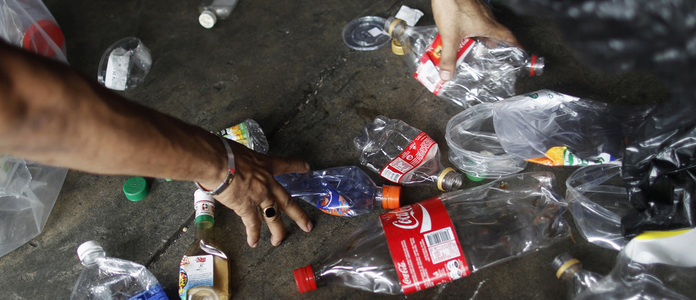 Worker separates plastic bottles at a recycling depot in Panama City September 12, 2013. The National Association for the Conservation of Nature (ANCON) reports that the majority of Panama City's beaches and rivers are contaminated with plastic and general waste due to lack of awareness for waste management, causing major problems for fishermen and negative impact on mangroves and their wildlife. According to the Plastic Oceans Foundation, more plastic has been produced over the last ten years than over the whole of the last century. Picture taken September 12, 2013. REUTERS/ Carlos Jasso (PANAMA - Tags: ENVIRONMENT SOCIETY) - GM1E99I1RKF01