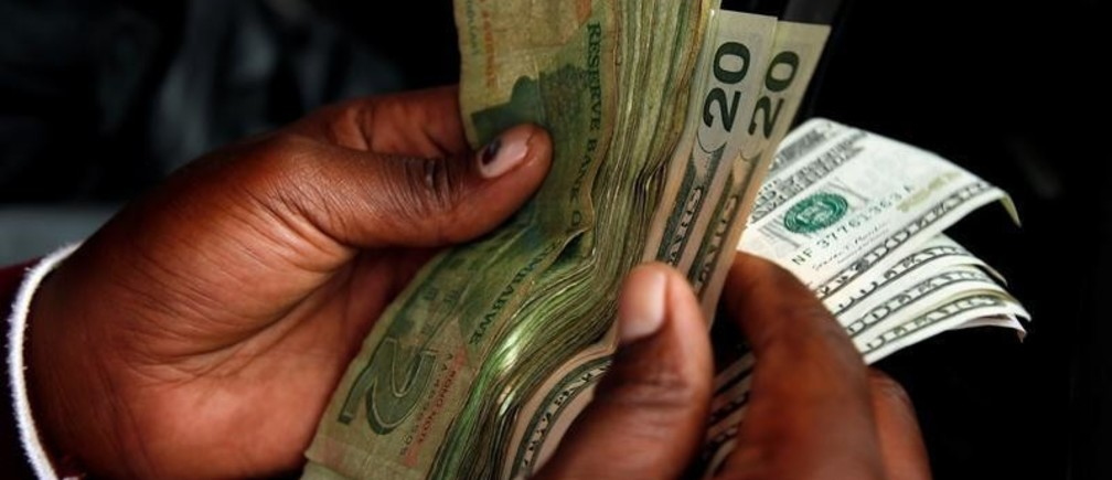 An illegal money changer counts dollar notes in Harare, Zimbabwe, January 10, 2019. REUTERS/Philimon Bulawayo - RC1827386890