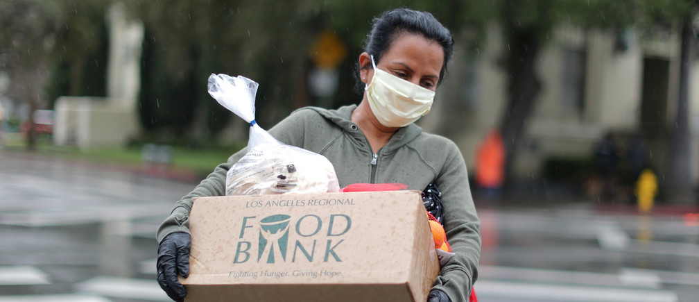 A woman carries away fresh food at a Los Angeles Regional Food Bank giveaway of 2,000 boxes of groceries, as the spread of the coronavirus disease (COVID-19) continues, in Los Angeles, California, U.S., April 9, 2020.  REUTERS/Lucy Nicholson - RC281G95ISBZ