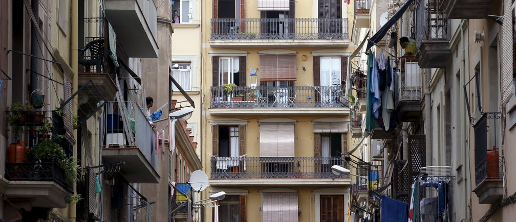 Men speak from balconies at Barceloneta neighborhood in Barcelona, Spain, August 18, 2015. Barcelona's new mayor is picking a fight with home rental websites as she tries to crack down on uncontrolled tourism that she fears could drive out poor residents and spoil the Catalan capital's charm. Picture taken on August 18, 2015. REUTERS/Albert Gea - GF10000182213