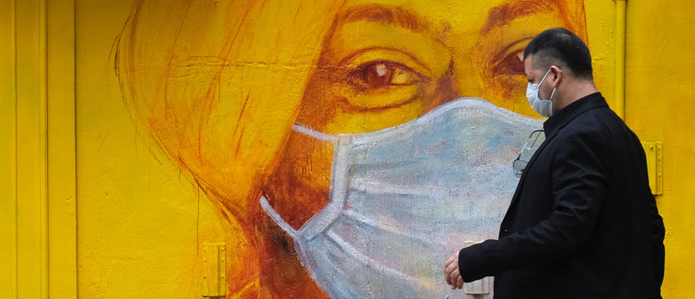 A man with protective mask walks on the street, following the novel coronavirus disease (COVID-19) outbreak, in Hong Kong, China March 27, 2020. REUTERS/Tyrone Siu - RC29SF9EMQ4W