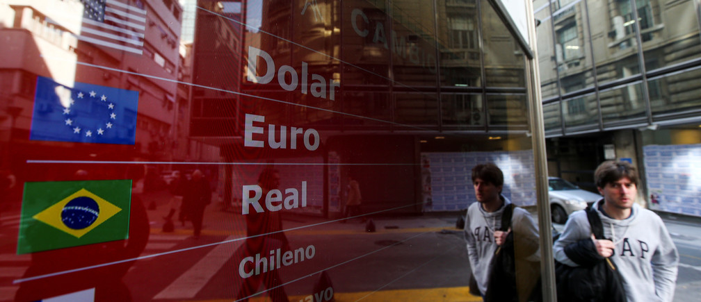 A man walks past an electronic board showing currency exchange rates, in Buenos Aires, Argentina August 20, 2019. REUTERS/Agustin Marcarian - RC17EF451D70