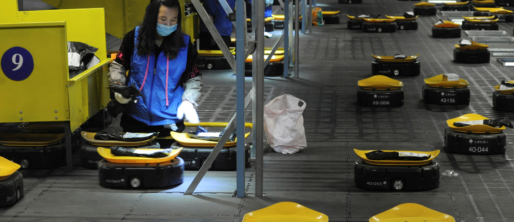 Employees sort parcels with automated guided vehicles (AGVs) at a logistic centre of a postal service a day ahead of the Singles' Day online shopping festival in Nanjing, Jiangsu province, China November 10, 2019. Picture taken November 10, 2019. REUTERS/Stringer  ATTENTION EDITORS - THIS IMAGE WAS PROVIDED BY A THIRD PARTY. CHINA OUT. - RC2S8D9J3HDP