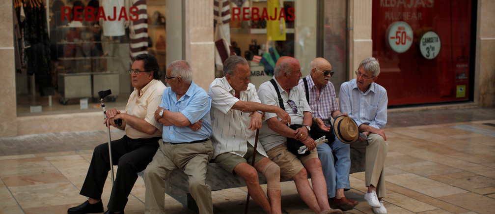 Pensioners sit on a bench at Marques de Larios street in downtown Malaga, Spain, July 4, 2016. REUTERS/Jon Nazca - S1AETNROHLAB