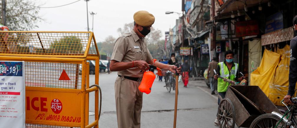 Un policier portant un masque de protection brandit sa matraque alors qu'il monte la garde pendant un confinement prolongé à l'échelle nationale pour ralentir la propagation de la maladie à coronavirus (COVID-19), dans les vieux quartiers de Delhi, en Inde, le 15 avril 2020.
