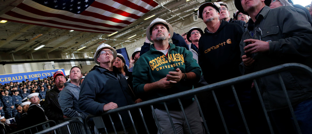 Shipbuilding workers watch on a video screen as U.S. President Donald Trump concludes his remarks aboard the pre-commissioned U.S. Navy aircraft carrier Gerald R. Ford at Huntington Ingalls Newport News Shipbuilding facilities in Newport News, Virginia, U.S. March 2, 2017. REUTERS/Jonathan Ernst - RTS117H0