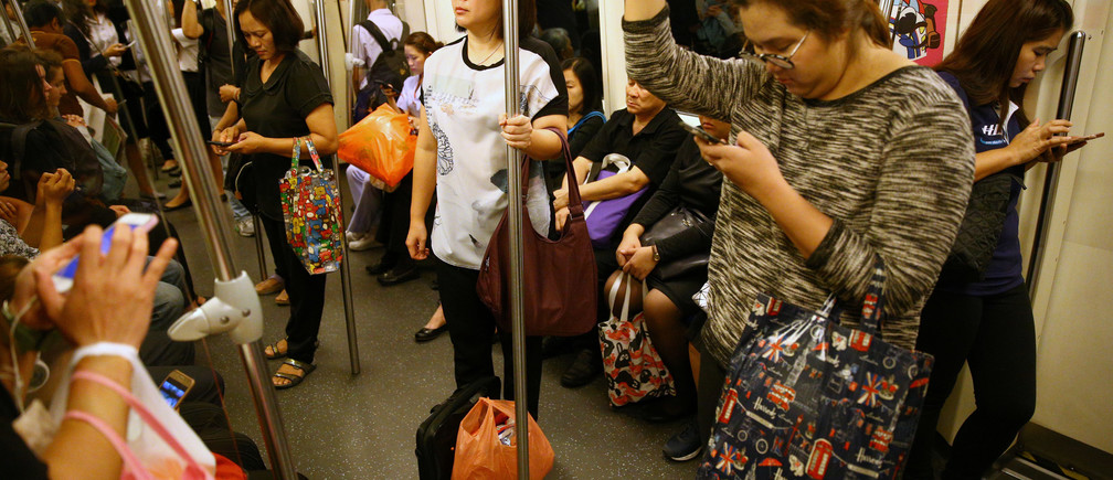Passengers use their mobile phones as they ride a train in Bangkok, Thailand, June 12, 2017.