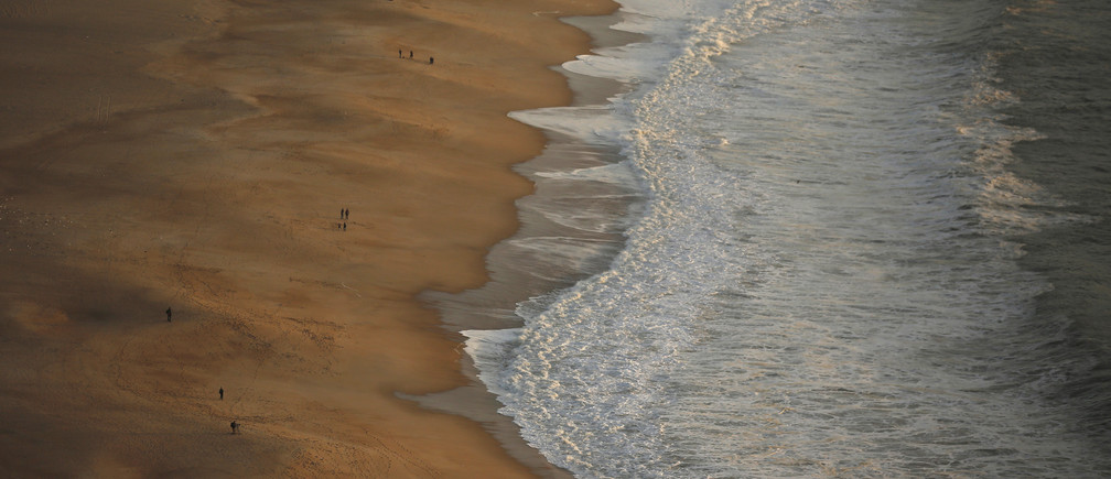 People walk at the beach in Nazare October 29, 2013.  REUTERS/Rafael Marchante (PORTUGAL - Tags: SOCIETY) - GM1E9AU0FUD01