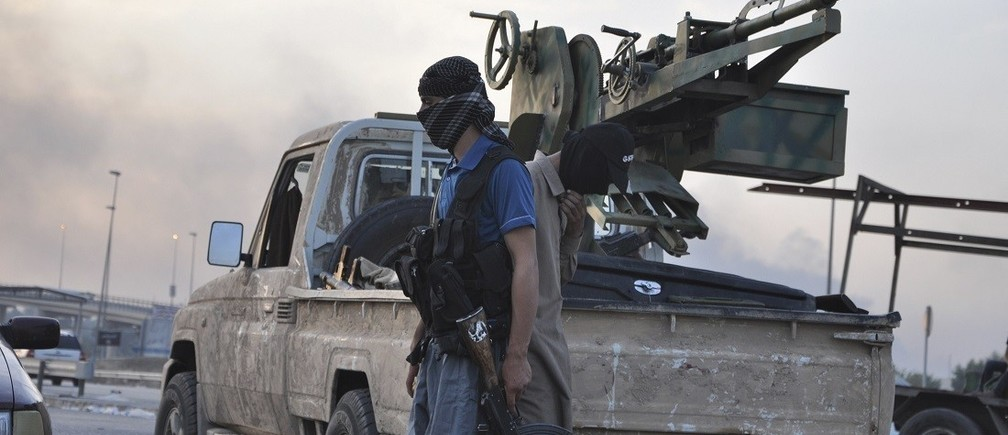 Fighters of the Islamic State of Iraq and the Levant (ISIL) stand guard at a checkpoint in the northern Iraq city of Mosul, June 11, 2014. Since Tuesday, black clad ISIL fighters have seized Iraq's second biggest city Mosul and Tikrit, home town of former dictator Saddam Hussein, as well as other towns and cities north of Baghdad. They continued their lightning advance on Thursday, moving into towns just an hour's drive from the capital. Picture taken June 11, 2014. REUTERS/Stringer (IRAQ - Tags: CIVIL UNREST POLITICS CONFLICT TPX IMAGES OF THE DAY) - RTR3TDRG