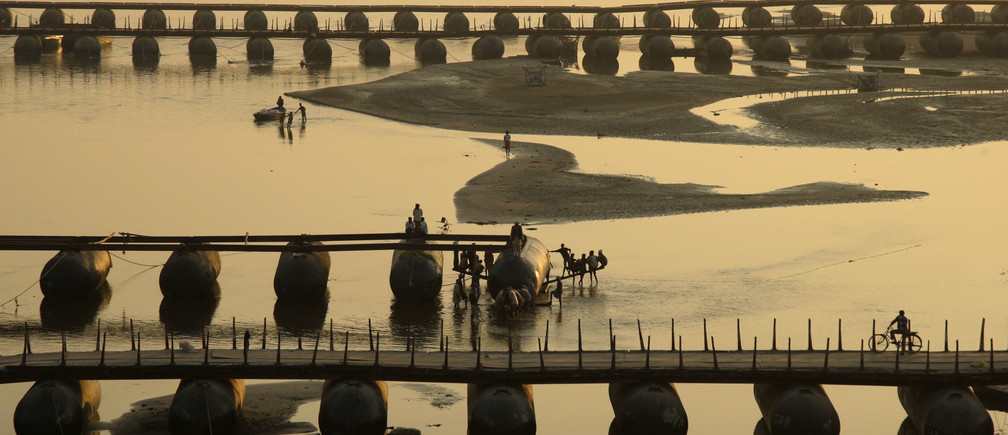 "Labourers work on an under-construction pontoon bridge spanning the river Ganga ahead of the ""Kumbh Mela"", or Pitcher Festival, as the sun sets in the northern Indian city of Allahabad December 2, 2012."