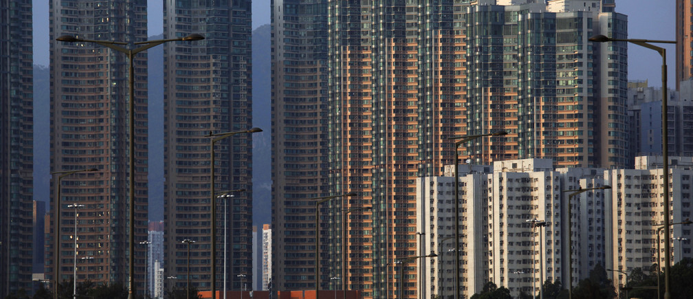 Light shines on a column of highrise residential towers during sunset in Hong Kong February 22, 2013. Hong Kong will impose new measures, including raising buyers' stamp duties, to cool its overheated property sector, which has some of the world's most expensive apartments, officials said on Friday. REUTERS/Bobby Yip (CHINA - Tags: BUSINESS ENVIRONMENT) - GM1E92M1FVB01