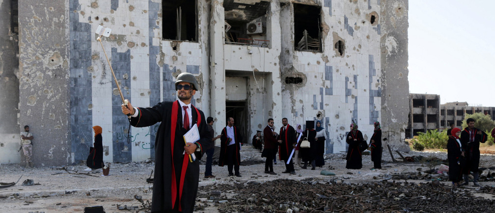 A new graduate of Benghazi University takes a selfie in front of a ruined building at his university former headquarters which was destroyed during clashes in 2014 between members of the Libyan National Army and Shura Council of Libyan Revolutionaries, an alliance of former anti-Gaddafi rebels who have joined forces with Islamist group Ansar al-Sharia, in Benghazi, Libya, October 27, 2016. REUTERS/Esam Omran Al-Fetori      TPX IMAGES OF THE DAY      - RTX2QRLO
