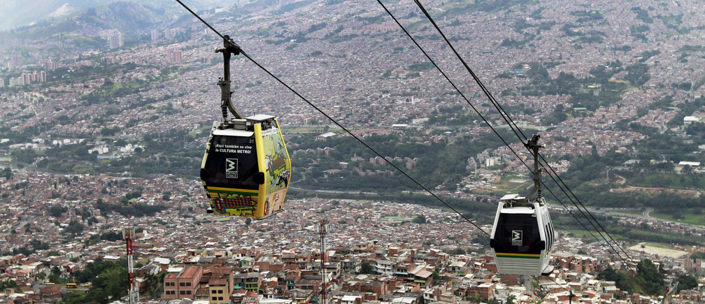 Cable cars pass above the town of Medellin March 1, 2013