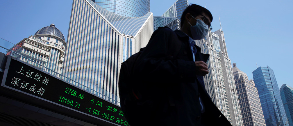 A pedestrian wearing a face mask walks near an overpass with an electronic board showing stock information, following an outbreak of the coronavirus disease (COVID-19), at Lujiazui financial district in Shanghai, China March 17, 2020. REUTERS/Aly Song - RC2FLF951HFT