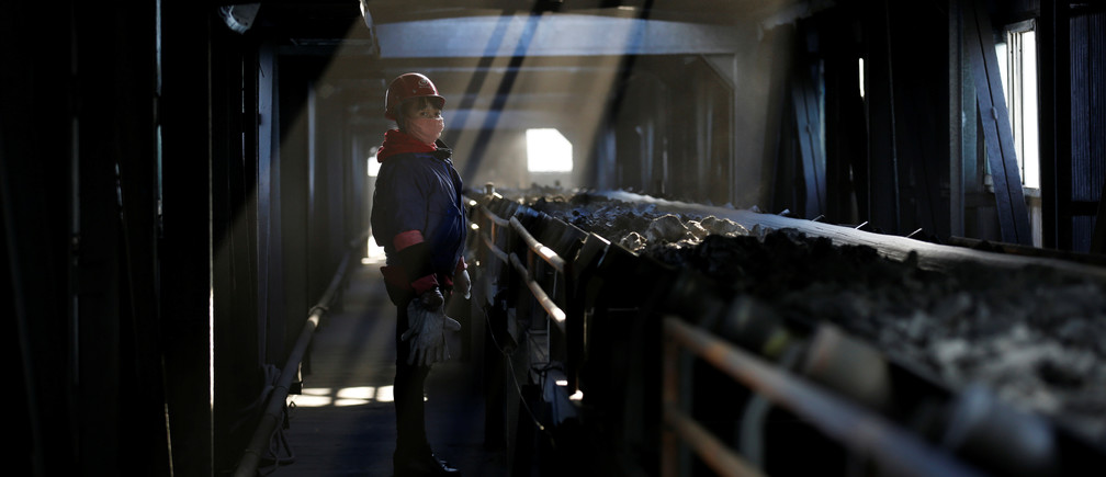 A worker inspects a conveyor belt carrying coal at a coal coking plant in Yuncheng, Shanxi province, China January 31, 2018.