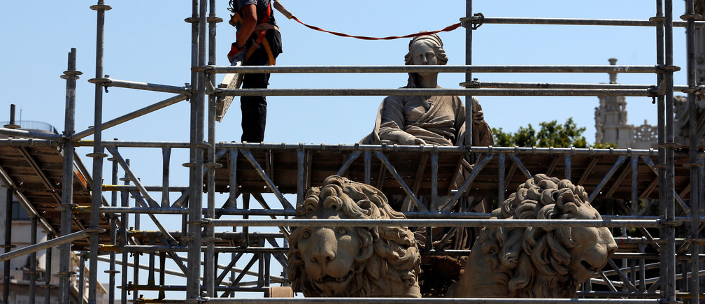 A construction worker sets up a scaffold around Cibeles Fountain in central Madrid, Spain,  July 27, 2016. Picture taken July 27, 2016. REUTERS/Sergio Perez - RTSK0YF