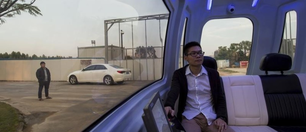 Zhang Jinming, who is in charge of the driverless car project, poses for a photo inside a driverless vehicle at Vanke's Building Research Centre in Dongguan, south China's Guangdong province, November 2, 2015. The country's largest property developer, China Vanke, is investing in its own robots to do certain jobs in the face of a labor shortage in the world's most populated country. This driverless car is among the robots that Vanke is aiming to bring in. Picture taken November 2, 2015. REUTERS/Tyrone Siu