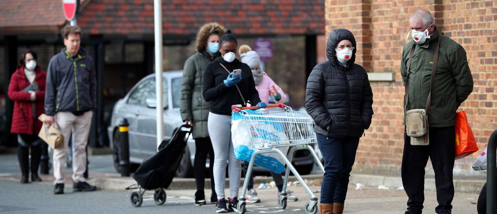 People wearing protective facemasks queue outside Sainsbury's supermarket in Streatham, as the spread of the coronavirus disease (COVID-19) continues, London, Britain, March 29, 2020. REUTERS/Hannah McKay - RC2NTF94H09S