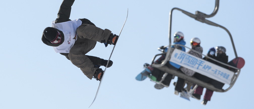 A snowboarding contestant takes a jump during a competition in Beijing, China, January 17, 2016. REUTERS/China Daily ATTENTION EDITORS - THIS PICTURE WAS PROVIDED BY A THIRD PARTY. THIS PICTURE IS DISTRIBUTED EXACTLY AS RECEIVED BY REUTERS, AS A SERVICE TO CLIENTS. CHINA OUT. NO COMMERCIAL OR EDITORIAL SALES IN CHINA.  - GF20000098599