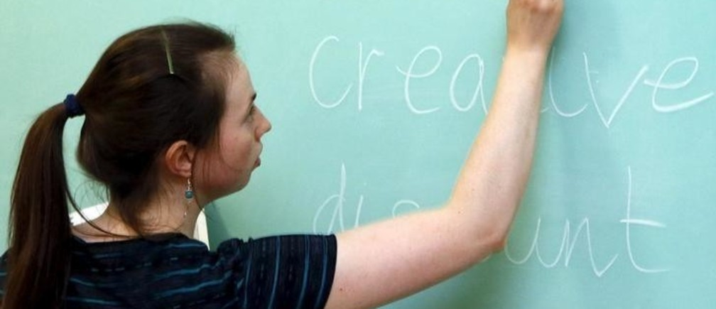 English teacher Laura Thomas, who is a British citizen,  writes on a blackboard as she conducts a lesson in the town of Lesosibirsk, north of the Russian Siberian city of Krasnoyarsk, April 24, 2015. Thomas, 25, a graduate of the University of Cambridge, developed an interest in the Russian language and culture as a teenager, and left her native town of Congleton, Cheshire in Britain for Lesosibirsk seven months ago to educate Russian trainee teachers in the English language at a local educational institute, a branch of the Siberian Federal University. Thomas has since experienced her first severe Siberian winter and has already made new acquaintances among the local residents. She plans to live and work in the region for at least several years to come.  REUTERS/Ilya Naymushin