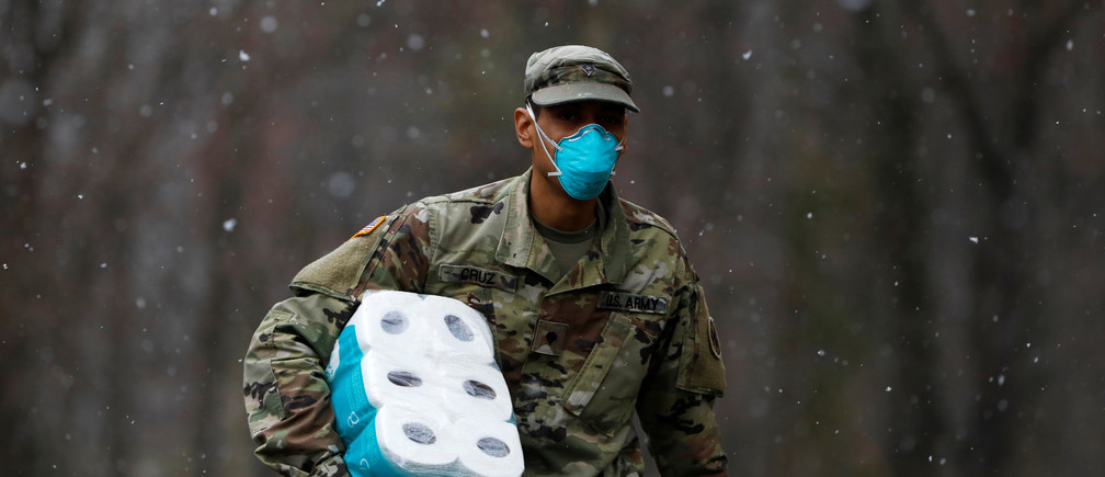 A member of Joint Task Force 2, composed of soldiers and airmen from the New York Army and Air National Guard, wears a face mask while carrying paper towels as he arrives to sanitize and disinfect the Young Israel of New Rochelle synagogue, as snow falls during the coronavirus disease (COVID-19) outbreak in New Rochelle, New York, U.S., March 23, 2020. REUTERS/Andrew Kelly - RC2RPF9XLLG9