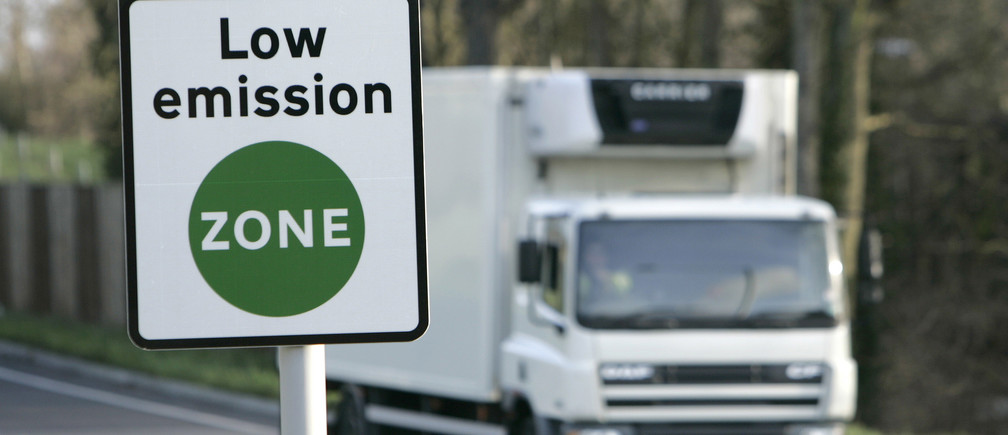 A vehicle passes a sign for the new Low Emissions Zone at Coulsdon in London February 3, 2008. Large vehicles that do not meet specific emission standards will be charged to travel within the London-wide zone, with the stated aim of improving the capital's air quality. The scheme comes into effect on Monday.        REUTERS/Luke MacGregor(BRITAIN) - GM1DXEKXDWAA