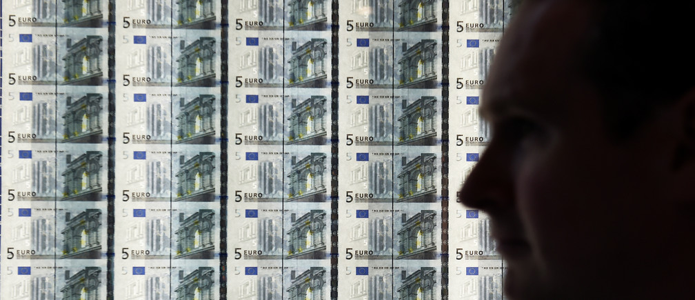 A man walks by a sheet of 5-euro notes at the opening of the new Central Bank of Ireland offices in Dublin.
