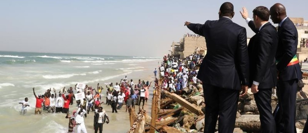 French President Emmanuel Macron (C) waves to people on the beach with Saint-Louis Mayor Mansour Faye and Senegalese President Macky Sall (L) during a visit to see the process that causes coastal erosion in Saint-Louis, Senegal, Febuary 3, 2018.   REUTERS/Ludovic Marin/Pool - RC150B7F9FE0
