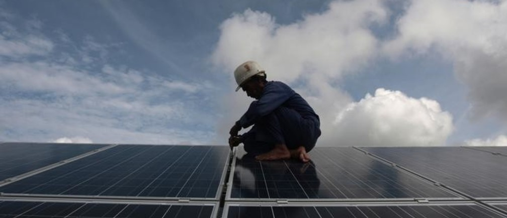 A worker adjusts solar panels at a park on the outskirts of Havana September 24, 2013. According to local media, the project is part of a joint venture between India and Cuba on renewable energy and initially plans to generate 1500 megawatts of electricity per hour.  REUTERS/Stringer (CUBA - Tags: ENERGY TPX IMAGES OF THE DAY BUSINESS)