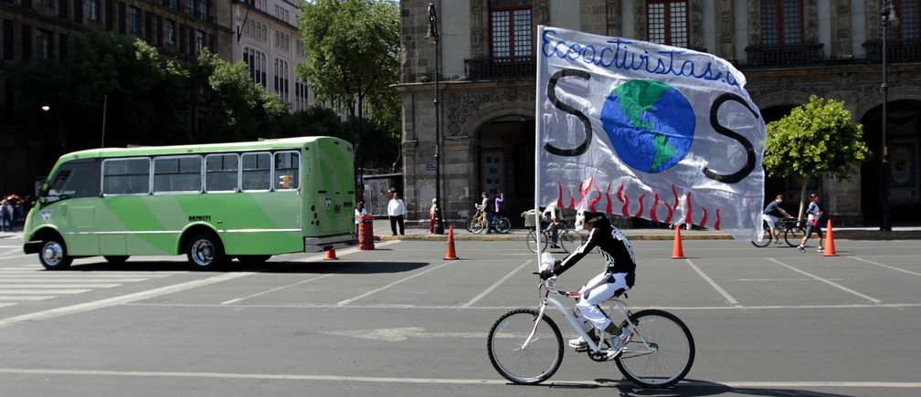 "A man wearing a skull mask rides his bicycle as he carries a giant banner, reading ""Ecotourists and a signal SOS "", at the main Zocalo square in Mexico City April 22, 2012.  REUTERS/Henry Romero (MEXICO - Tags: SOCIETY) - RTR313GI"